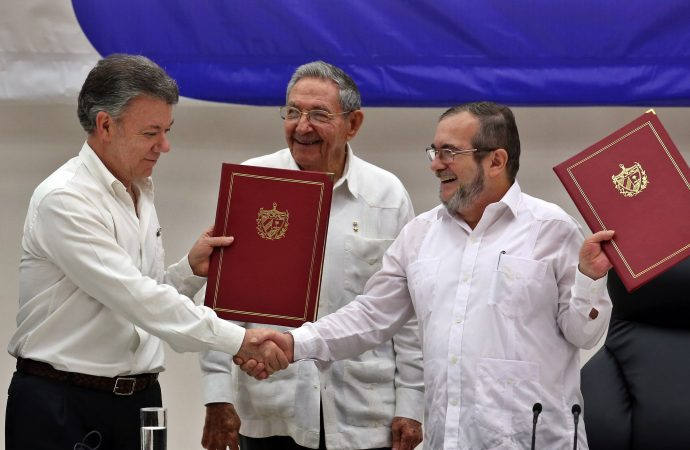 Colombian President Juan Manuel Santos, left, shakes hands with FARC boss 'Timochenko' in Havana June 23 as Cuban President Raúl Castro looks on. (Credit: CNS photo/Alejandro Ernesto, EPA.)